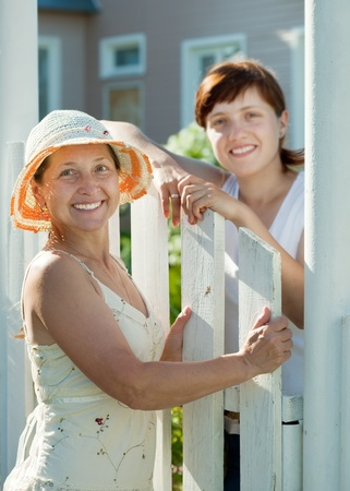Two happy women near fence wicket. Selective focus on left woman only Stock Photo - 11479981