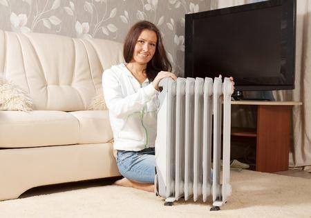 smiling woman  near warm radiator  in home Stock Photo - 11479955