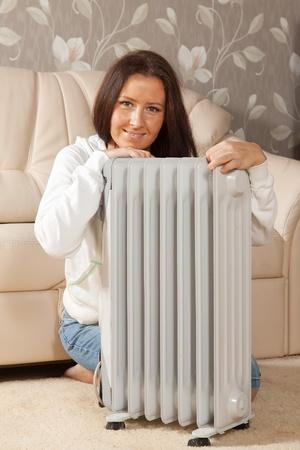radiador: mujer, sonriente, cerca del radiador caliente en el hogar