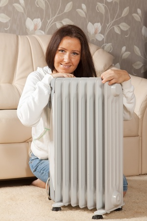 calorifer:  smiling woman   near warm radiator  in home