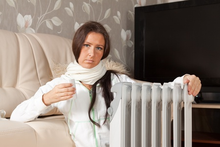 woolley:   woman   near warm radiator  in home