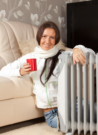 smiling woman  with red cup near oil heater