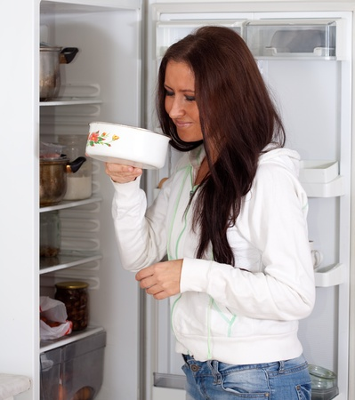 frowy: woman  holding foul food  near refrigerator  at home Stock Photo
