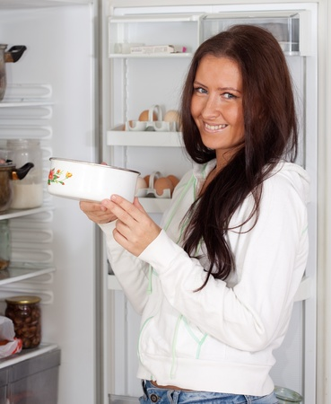 woman with saucepan  near refrigerator  at home Stock Photo - 11479935