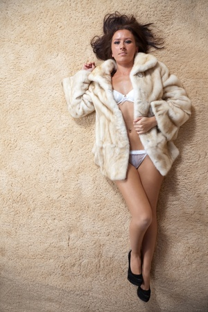 Sexy woman in fur coat over  carpet photo