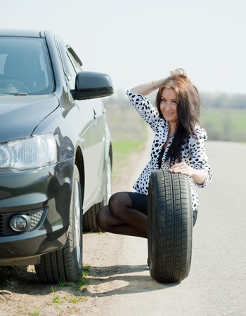 Woman changing car wheel at road photo