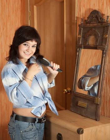 Girl combing  hair in home interior photo