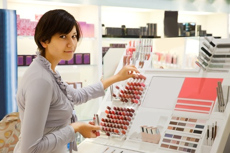 young girl is buying lipstick at cosmetics  shop photo