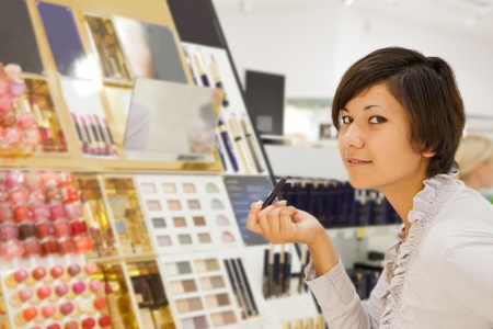 young woman chooses the cosmetic  at cosmetics  shop photo
