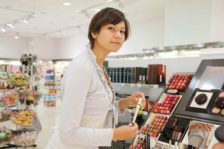 young woman chooses the mascara at cosmetics  shop photo