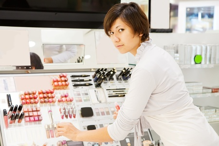young woman chooses the cosmetic  at cosmetics  shop Stock Photo - 11479762
