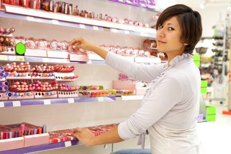 kosmetik: junge Frau w�hlt den kosmetischen bei Kosmetik-Shop