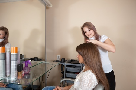 hairtician: Female hair stylist working with long-haired girl Stock Photo