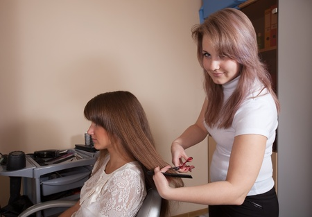 hair stylist: Female hair stylist working with long-haired girl Stock Photo