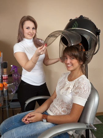 Female hairdresser working with hair dryer photo