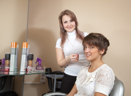 Female hairdresser working with long-haired girl. Focus on customer photo
