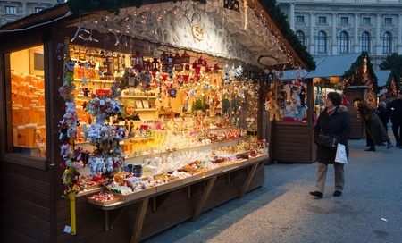 VIENNA, AUSTRIA - NOVEMBER 22: People walking at  Christmas Market at Maria-Theresien-Platz   in November 22, 2011 in Vienna, Austria. It sells Christmas gifts, candy and punch Stock Photo - 11400522