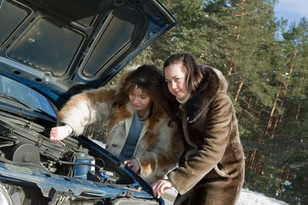 Two young  women  trying to fix the car photo