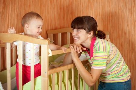 Happy mother with her baby in crib photo