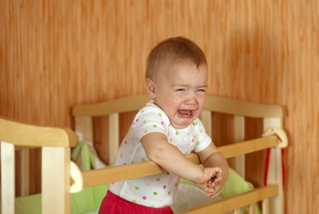 Crying baby of one year old  in crib photo