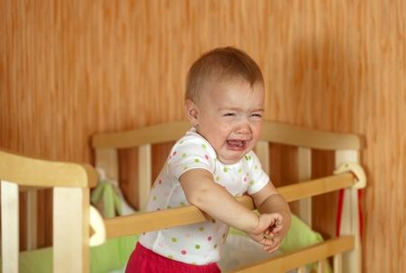 child crying: El llanto de la bebé de un año en la cuna Foto de archivo