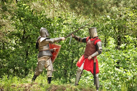 duel: Two knights in armor fights in forest