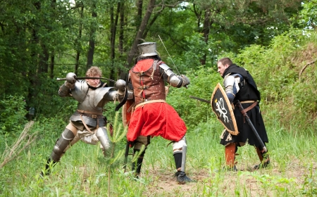 three knights in armor is fighting  at forest