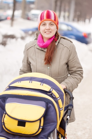 Young woman with pram in winter park photo