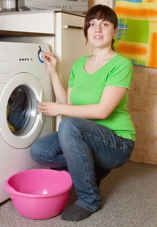 Beautiful women loading the washing machine. Cleaning and Laundry photo