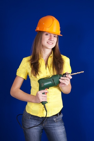 Female construction worker in a hard hat with drill over blue background photo