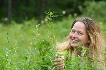 hanf: Gl�ckliche Frau mit frischem Hanf bei Cannabis-Pflanze