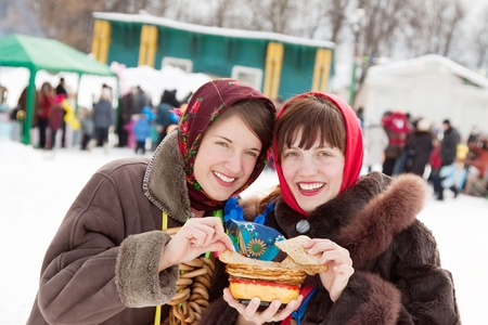 Women in traditional  clothes tasting pancake  during  Shrovetide photo
