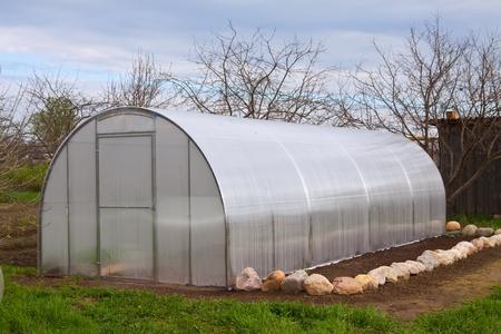 Nieuwe moderne kas in de tuin in het voorjaar Stockfoto