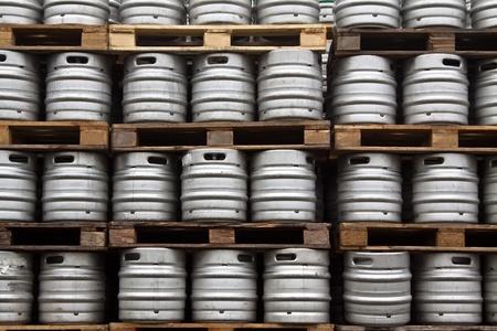 Many metal kegs of beer in regular rows photo