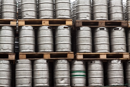 Many metal kegs of beer in regular rows photo