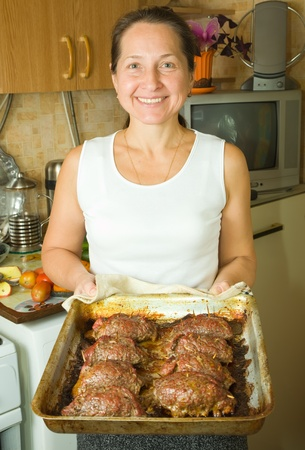 roasting pan: Mature woman with cooked stuffed beef on roasting pan in kitchen. One of the stages of preparation of  stuffed beef.  See series Stock Photo