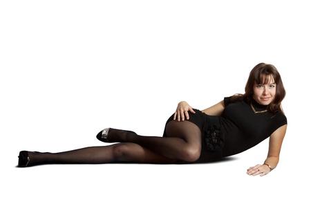 pantimedias: Chica sexy en el vestido negro se extiende sobre el fondo blanco Foto de archivo
