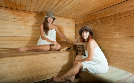 stive: Two girls in white sheet sits on bench at sauna