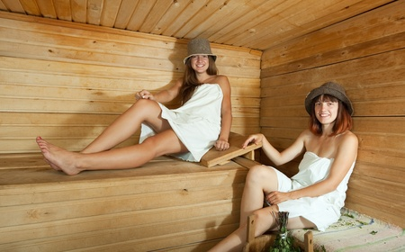 stive: Happy girls sitting on wooden bench in sauna