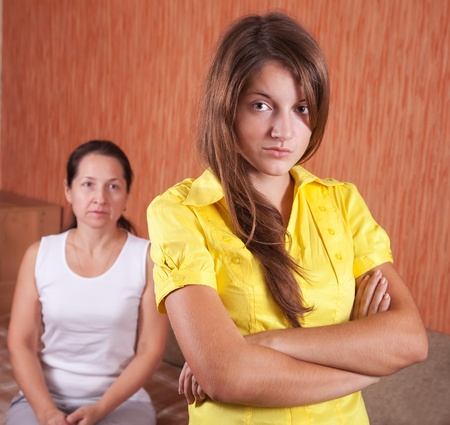 Mature mother and teenager daughter after quarrel at home photo