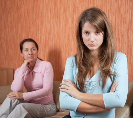 daughter and mature mother having quarrel at home photo