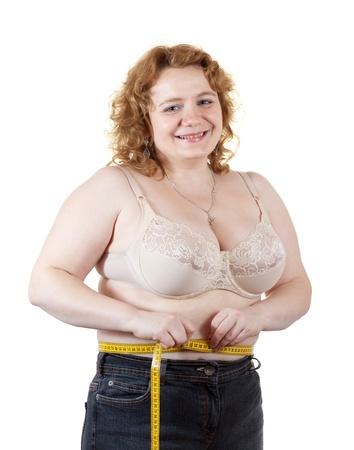 regordete: mujer gorda medir la cintura. Aislado sobre fondo blanco Foto de archivo