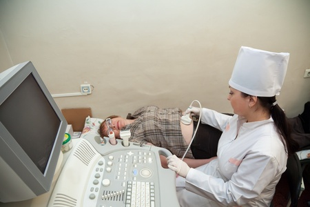 Female doctor making ultrasound investigation in medical clinic photo