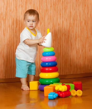 Baby girl plays with toys  in home interior photo