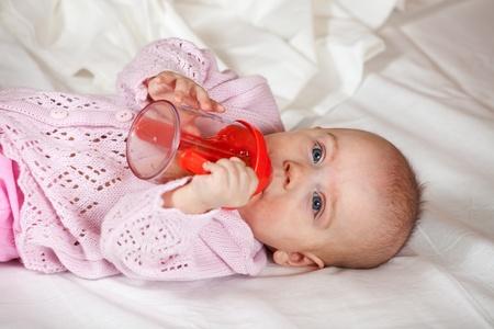 babygro: Baby girl of 5 months witn baby bottle on white sheet