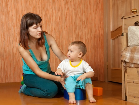 pissing: Mom puts the baby on the potty at home Stock Photo