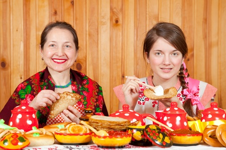 Women in traditional  clothes eating pancake during  Shrovetide Stock Photo - 11883184