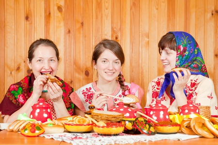 Women in traditional clothes celebrating Shrovetide and eats pancake  photo