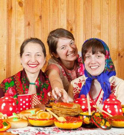banket: Happy mother with  daughters eating pancake with caviare during  Shrovetide