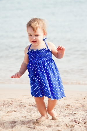 Baby girl walking on sand beach photo